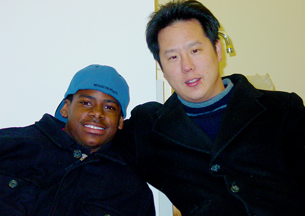 Dwaine Brown leans in close for a half hug with Steve Park as they pose for a photo inside a room.