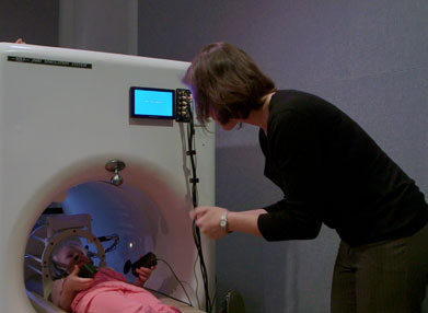 A girl acclimates to the MRI environment while a woman looks on.