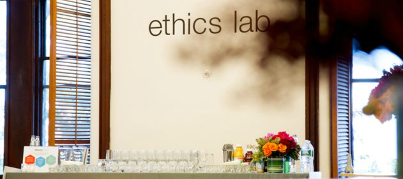 A table with refreshments sits in front of the Ethics Lab logo