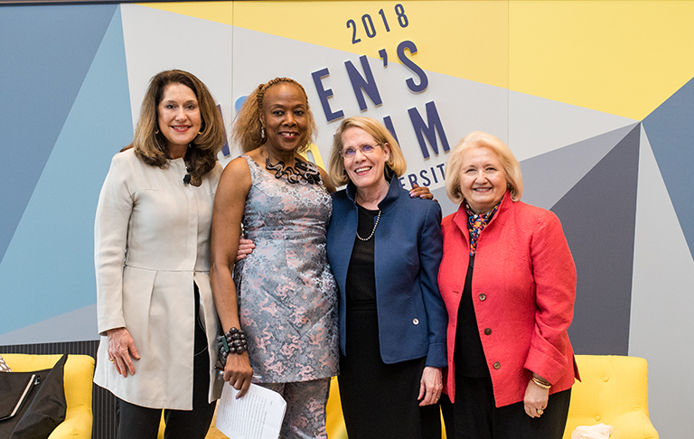 Jane Aiken, Rosemary Kilkenny, Judith Areen and Melanne Verveer pose in front of the 2018 Women's Forum sign.