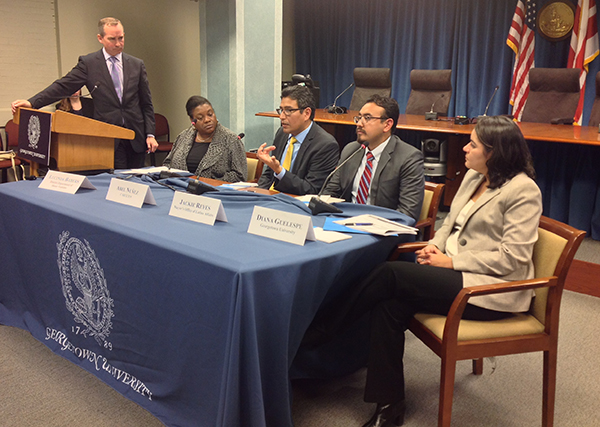 Standing, Chris Murphy, vice president for government relations and community engagement at Georgetown, listens as Abel Núñez, seated second from left, discusses the difficulties undocumented immigrants face in obtaining drivers' licenses.