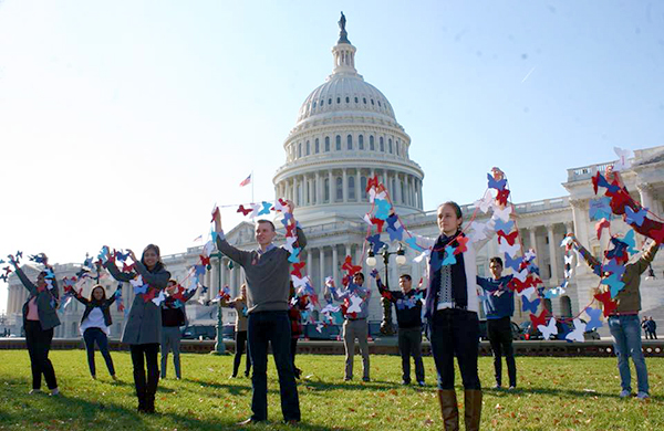 Students stand on the Capitol lawn with the Capitol building in the background holding up paper butterflies in support of Dreamers.