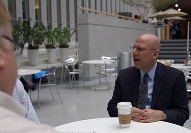 Joel Hellman, with a cup of coffee in front of him, speaks with companions at a table.