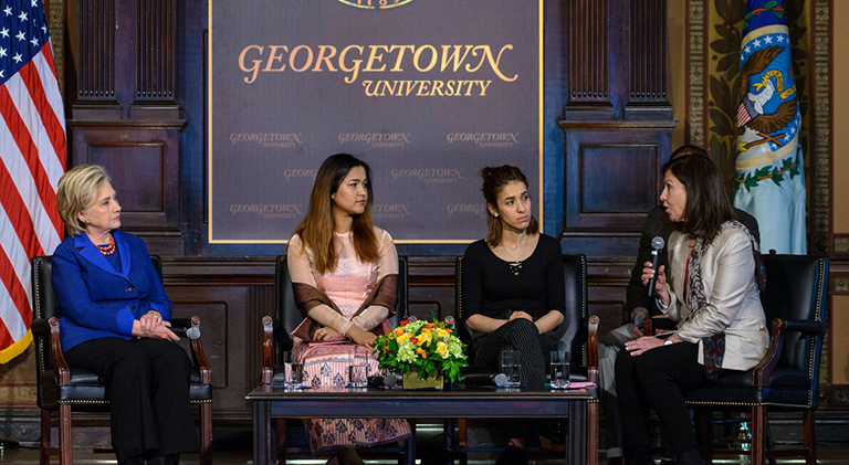 Hillary Rodham Clinton listens, seated, along with Wai Wai Nu and Nadia Murad as Lyse Doucet speaks during their panel discussion.