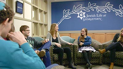 "Students smile and talk beneath a painted wall that reads ""Jewish Life at Georgetown."""