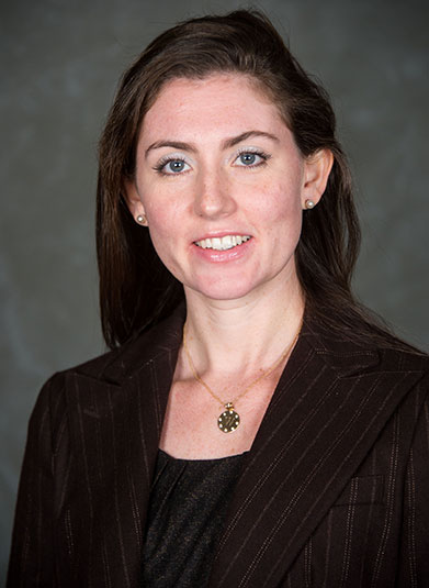 Anna Johnson, dressed in a brown suit, smiles in a headshot.