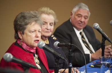 Carol Lancaster speaks with a microphone at a table while Madeleine Albright and Harold White look on