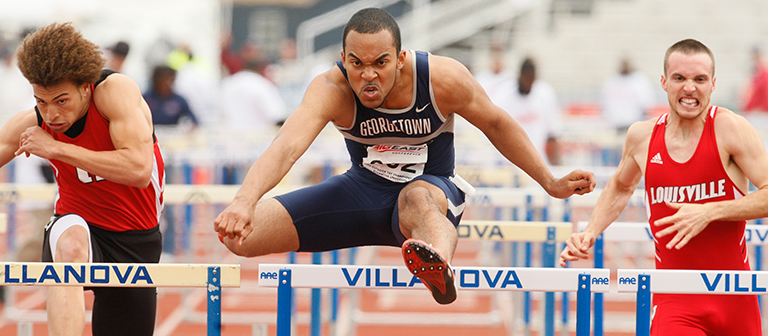 This 2008 photo shows Christopher Kinney clearing a track hurdle as two competitors close in on him during a race.
