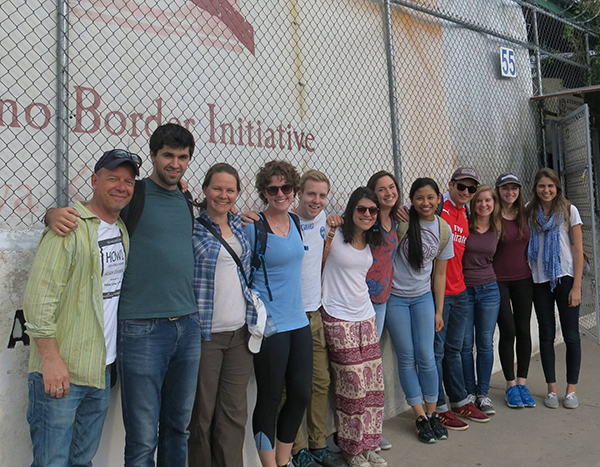 Tomas Alvarez Belon stands with members of the Georgetown community in front of a fence at the Kino border with the Kino Border initiative printed on a wall behind them.