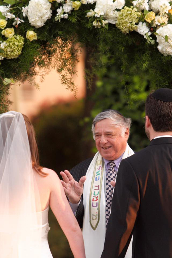 Rabbi Harold White presides over a marriage ceremony as the bride and groom stand before him.
