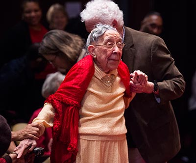 Daisy Pebbles Sewell, 95, stands with assistance from an audience member to cheers and applause.