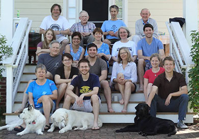 Dean Lancaster sits on some steps with her extended family and three dogs.