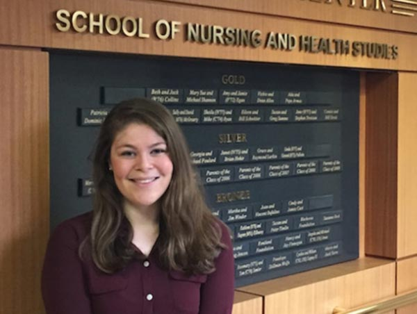 "Jennifer LaPier stands in front a sign reading ""School of Nursing and Health Studies"""