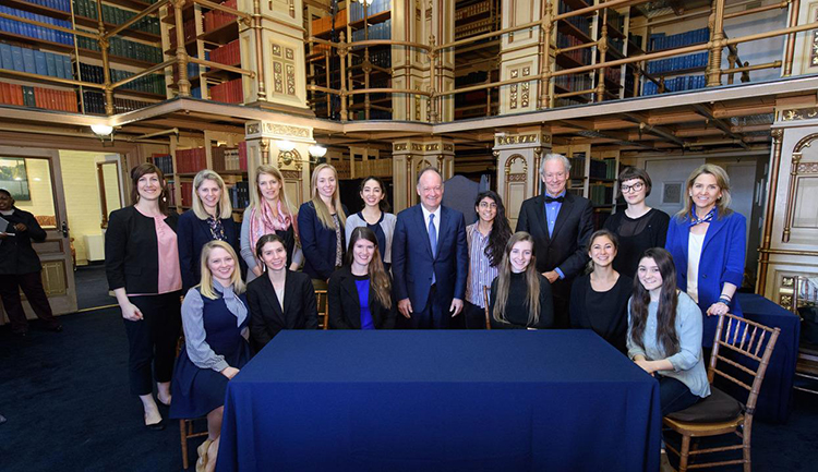 University leaders, Bill McDonough and students standing and sitting around a table in a library
