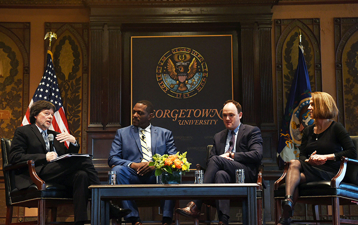 Ken Burns, Jule Hall, Max Kenner and Lynn Novick on stage with American flag and Georgetown University sign