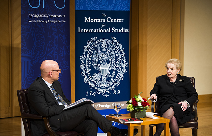 Joel Hellman and Madeleine Albright onstage with banners for the School of Foreign Service and the Mortara Center