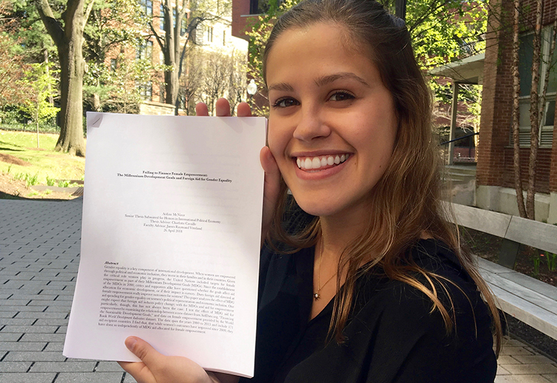 Aislinn McNiece sits on a bench outside holding a copy of her senior thesis