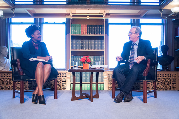 Tracy K. Smith and Paul Elie sitting in chairs in front of large windows in Riggs Library