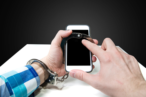 one hand handcuffed to a smartphone with free handing tapping on screen