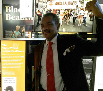 Maurice Jackson stands near a museum exhibit featuring Angela Davis with his fist in the air.