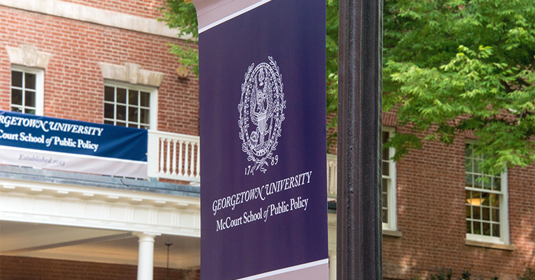 A McCourt School of Public Policy banner hangs on a lampost in front of the red brick Old North building.