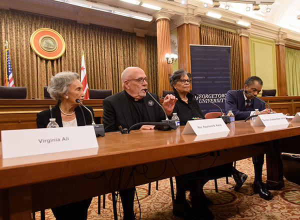 Rev. Raymond Kemp talks during a panel discussion with Virginia Ali and Charlene Drew Jarvis sitting on each side of him listening as Maurice Jackson sits to the far right listening and writing.