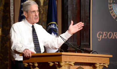 Robert Mueller speaks behind a podium on Gaston Hall's stage.