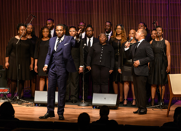 Nolan Williams Jr. leads the audience in song as a group of singers performs on stage behind him.