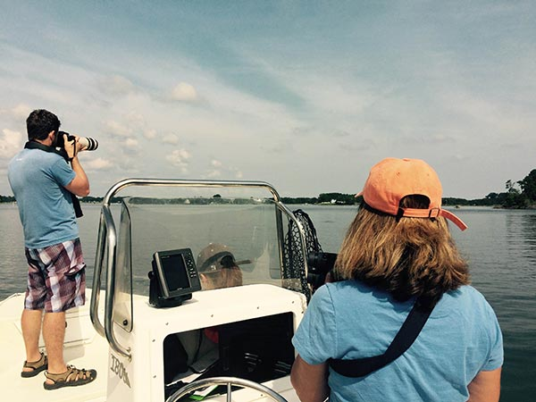 Janet Mann stands behind the boat's steering wheel as a student takes photographs of dolphins in the Potomac River.