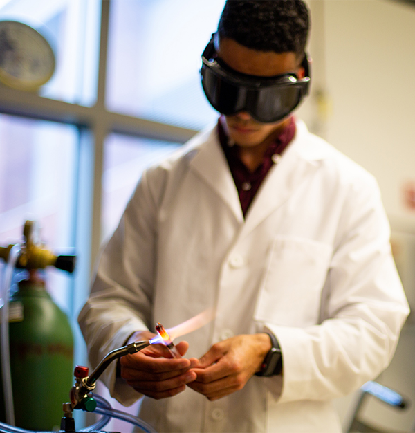 Orlando Stewart works in the chemistry lab using a flame to heat materials.