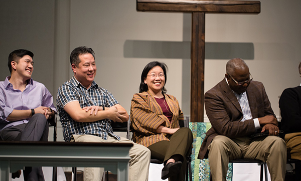 Steve Park and three other panelists sit on stage smiling at and talking to the audience in a church with a large wooden cross in the background.