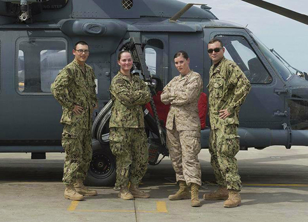 Cristine Pedersen stands in front of a helicopter dressed in camouflage with one female and two male members of her unit.
