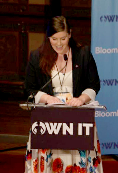 Cristine Pedersen looks down as she speaks at a lectern in Gaston Hall with the OWN IT Summit sign in front.