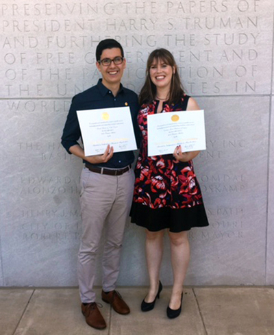Daniel Wassim and Cristine Pedersen stand together smiling in front of a gray stone building holding their Truman Scholarship certificates.