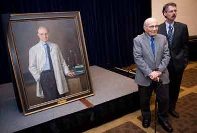 Dr. Edmund Pellegrino and Dr. Howard Federoff, executive vice president for health sciences and executive dean for the School of Medicine at Georgetown, stand in front of a portrait of the bioethics pioneer.