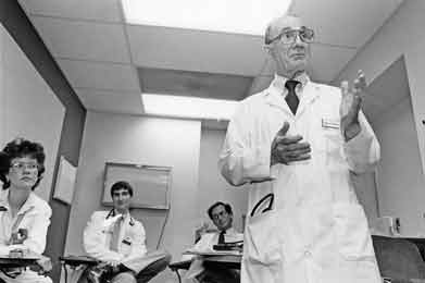 A black and white photo, taken in the 1980s, shows Dr. Edmund D. Pellegrino teaching in a classroom as students look on.