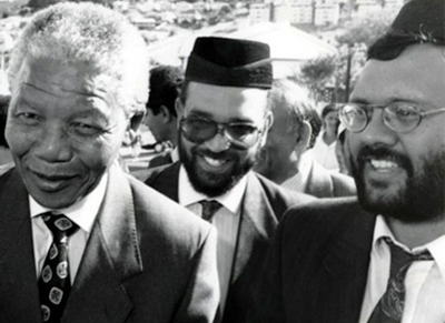 Ebrahim Rasool stands behind Nelson Mandela at an event in South Africa.