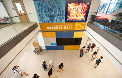 An overhead shot of Regents Hall depicts students with backpacks walking through the building.