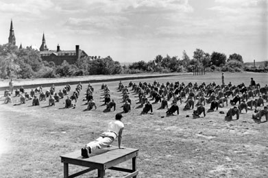 Men perform pushups on the lawn during army physical training at Georgetown during 1940s
