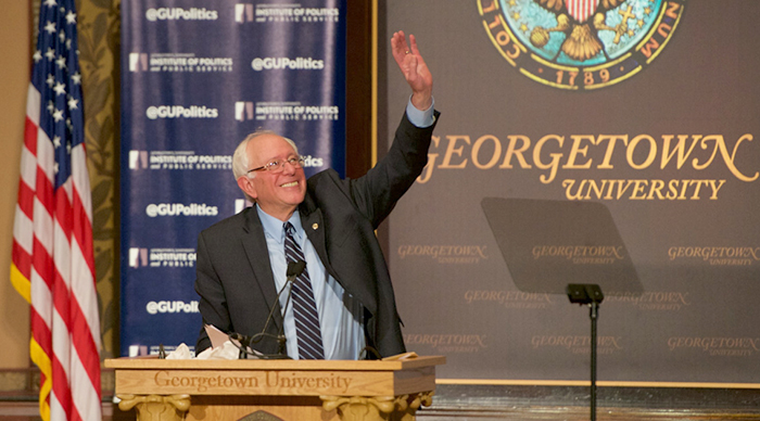 Senator Bernie Sanders smiles and waves to the crowd as he begins a speech from the podium onstage in Gaston Hall.