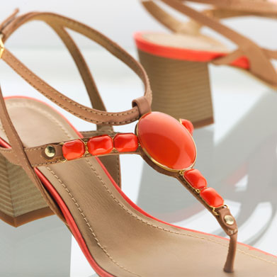 A closeup of strappy, high heel sandals bejeweled in orange stones.