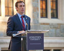 Danieal Feehan speaks at a lectern in front of White-Gravenor Hall at Georgetown