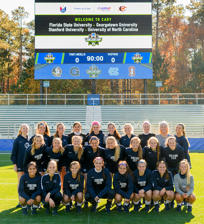 Members of the women's soccer team pose together on the filed in three rows with autumn-leaved trees in the background.