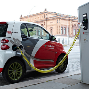 red and white electric car hooked up to charging station