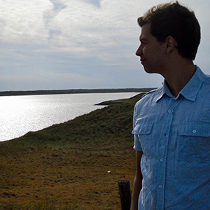 Dagomar DeGroot, standing on shore, looking at water