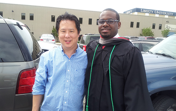 Dwaine Brown, dressed in a graduation robe, and Steve Park pose together in front of cars after Brown's graduation from Liberty University.