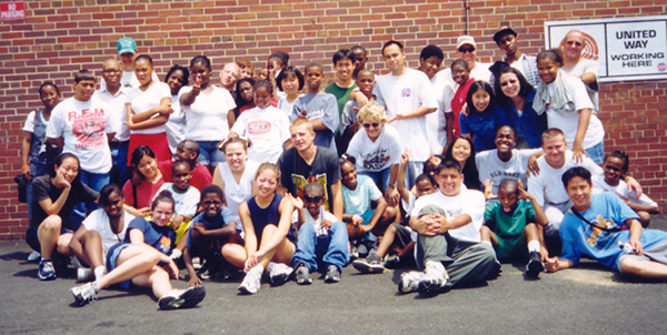 Steve Park poses outside in front of a brick building with a group of Little Lights students and volunteers.