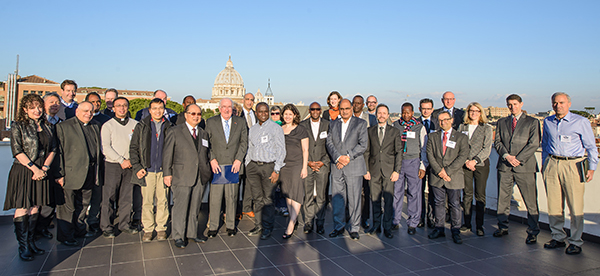 workshop participants pose with the Vatican City skyline in the background