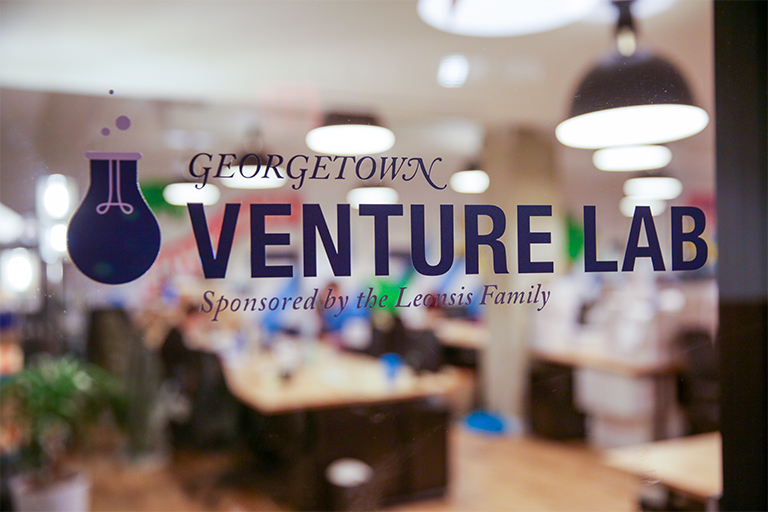 "Glass window reads ""Georgetown Venture Lab, Sponsored by Leonsis Family"" that overlooks brightly lit workspace."
