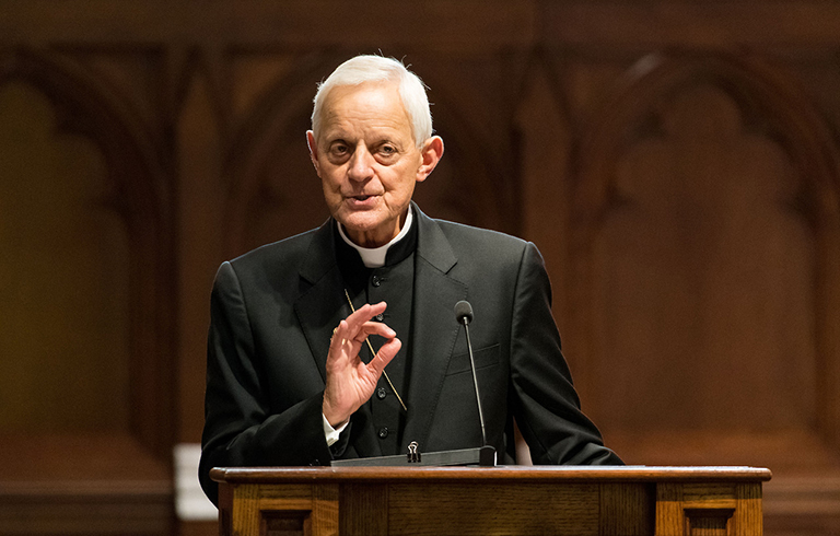 Cardinal Donald Wuerl speaks at a wooden lectern in Dahlgren Chapel with the building's interior woodwork displayed in the background